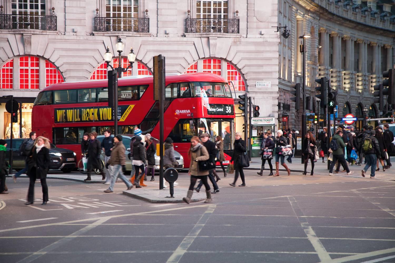 Imagen de peatones y un autobús rojo de dos pisos en las calles de Piccadilly Circus.