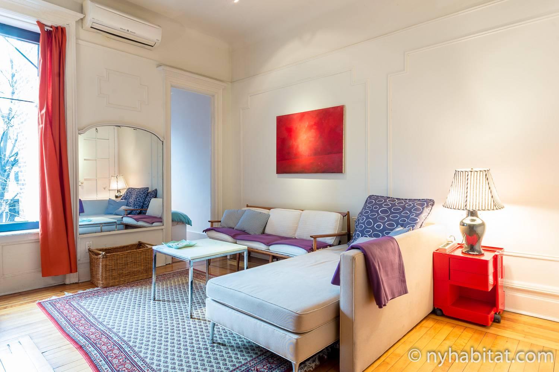 Imagen del salón del NY-16215 con sofá, mesita auxiliar y lámpara.