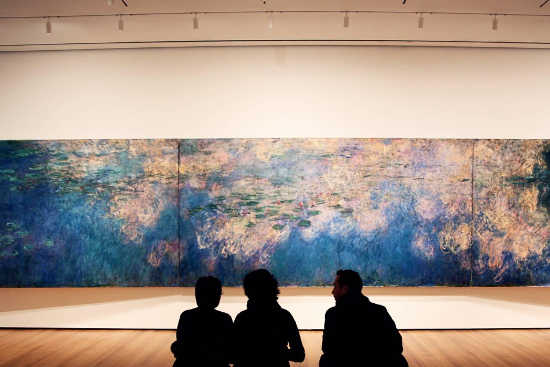 Imagen de gente sentada en frente de la pintura Los reflejos de las nubes en el estanque de lirios de agua de Claude Monet