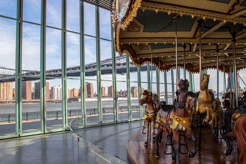 Imagen del Jane's Carousel en Brooklyn con las vistas al paisaje de Nueva York.