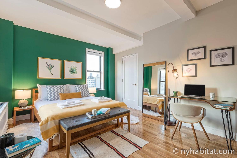 Imagen del dormitorio del apartamento NY-17625 con una cama de matrimonio, un escritorio y cuadros.