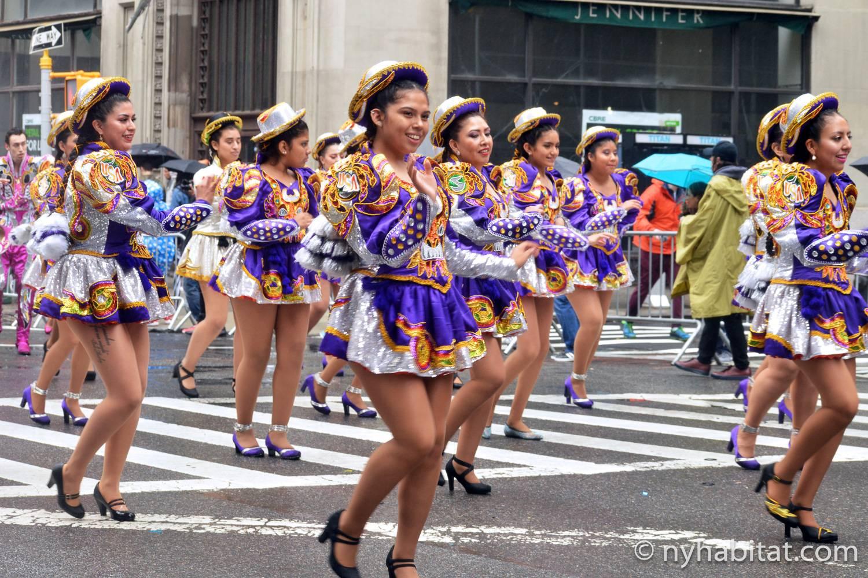 Imagen de bailarines vestidos con disfraces morados mientras bailan en la Dance Parade de la ciudad de Nueva York.