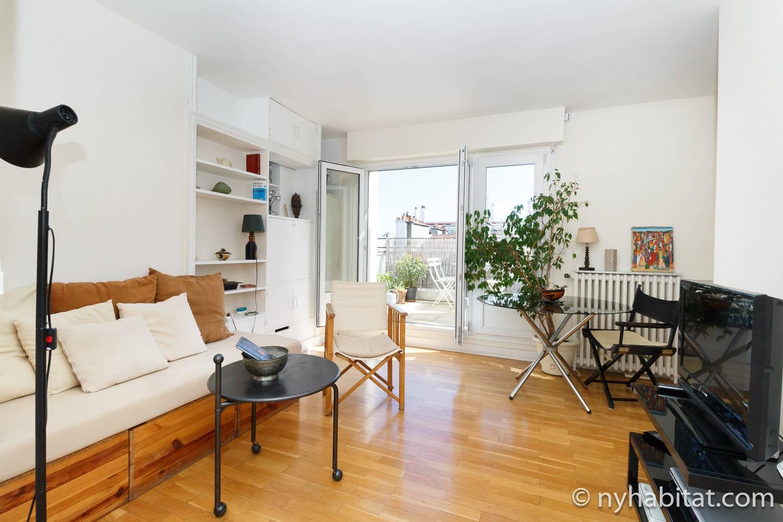 Imagen del salón en PA-3384 con sofá, sillas, mesas y una estantería.