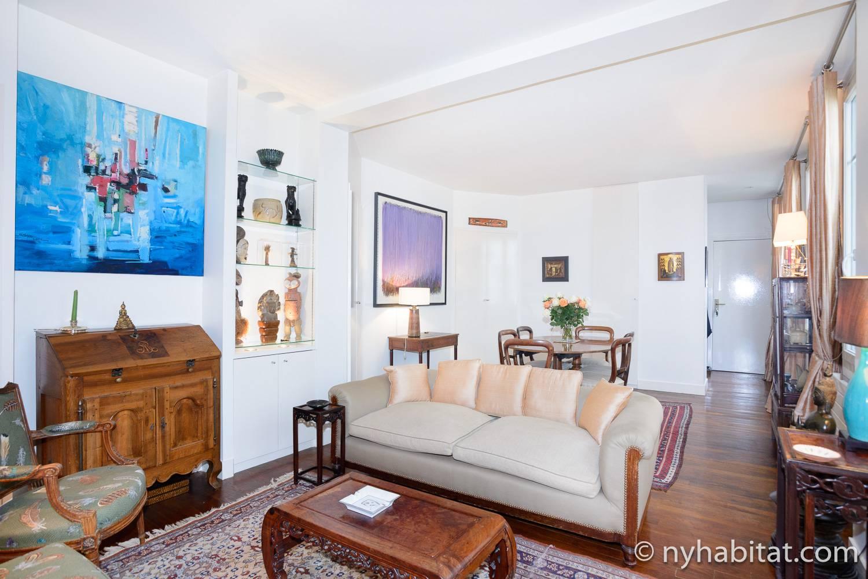 Imagen del salón en PA-4526 con sofá, mesa de café y obras de arte.