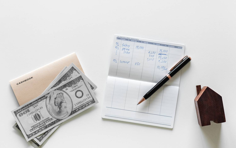 Imagen de dinero en efectivo, talonario y una casa modelo para representar el pago de una fianza.