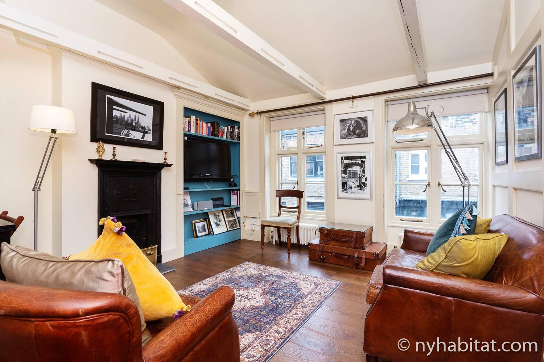 Imagen del salón de LN-1973 con una chimenea decorativa, sofás, televisión y obras de arte.