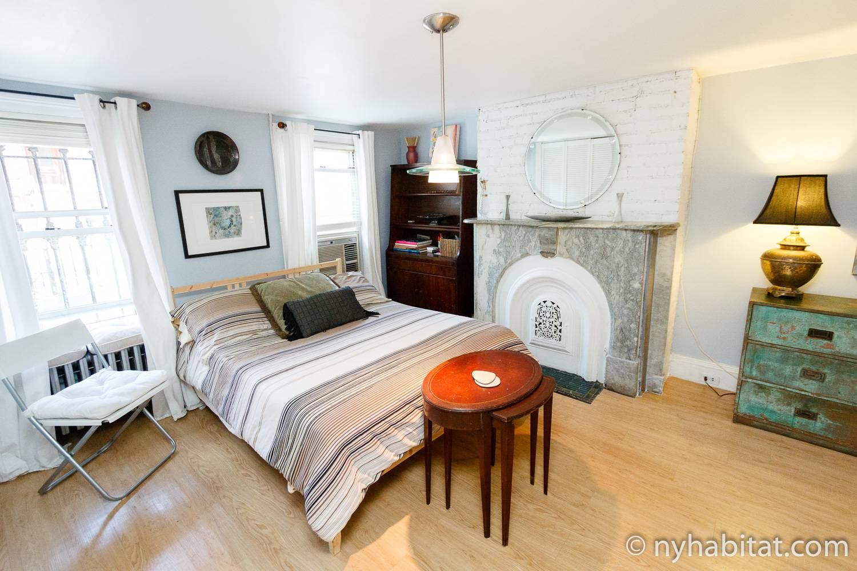 Imagen del salón del NY-16024 con una cama de matrimonio, una estantería y una chimenea decorativa.