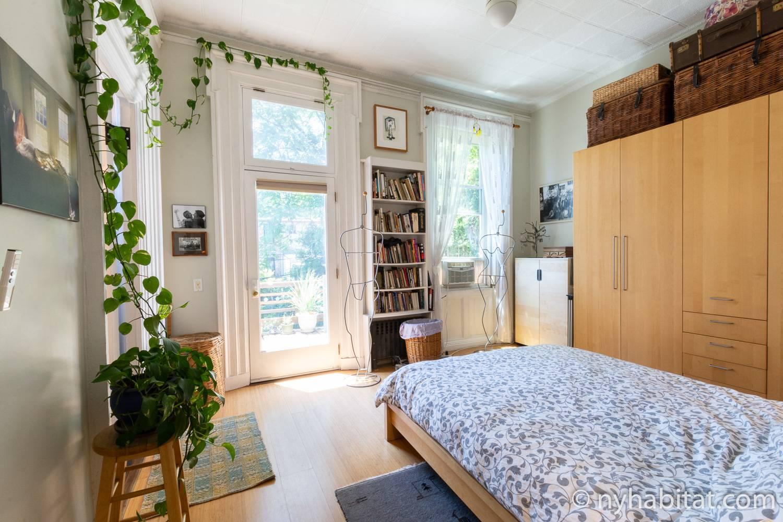 Imagen del dormitorio del NY-17602 con una cama de matrimonio, estantería, plantas, armario, obras de arte y puerta a la terraza exterior.