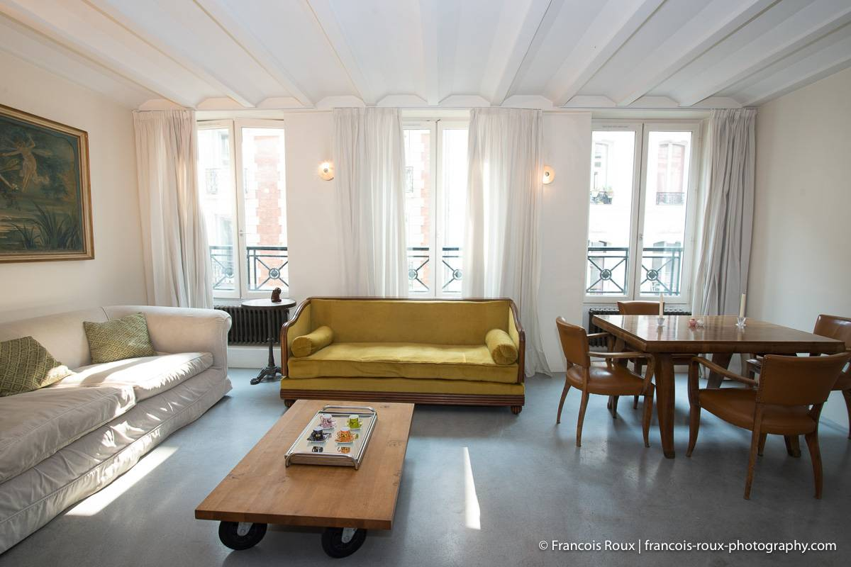 Imagen de la sala de estar en PA-4099 con un sofá y ventanas francesas.