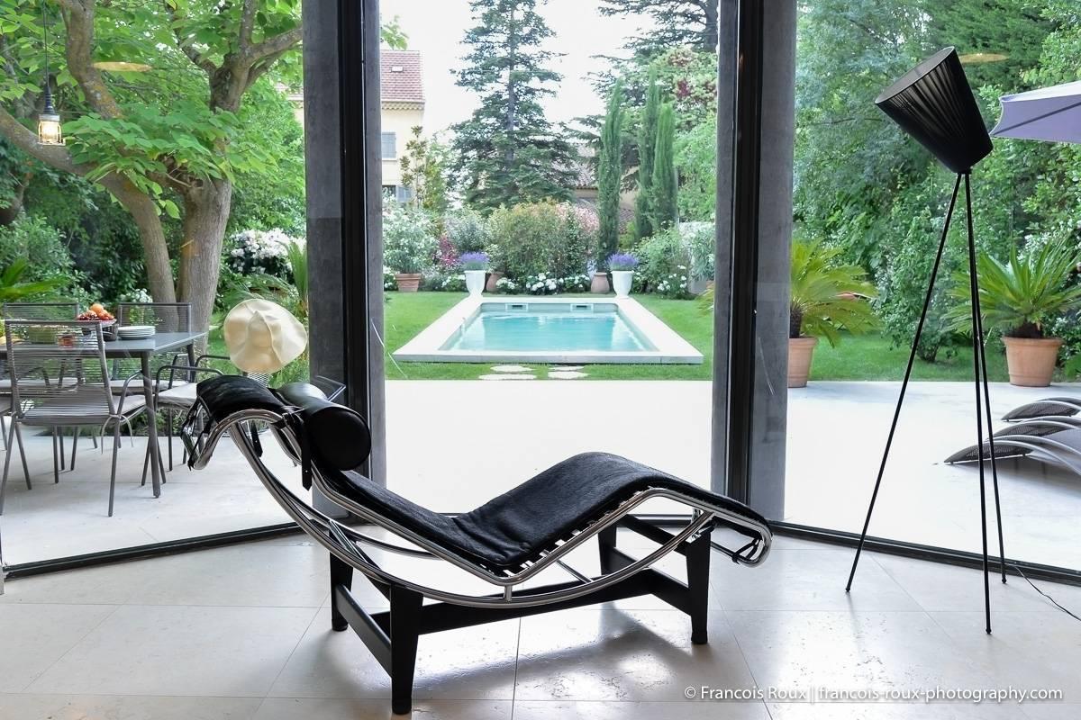 Imagen de la sala de estar en PR-1165 con sillón, ventanas grandes y patio trasero.