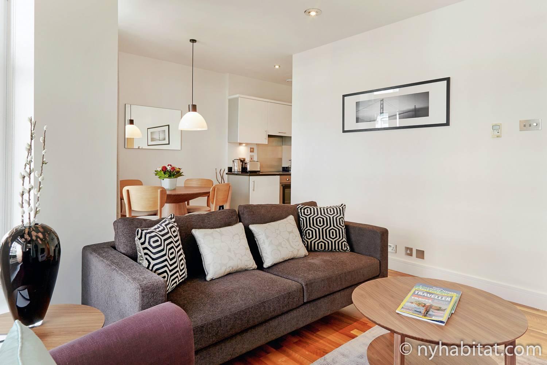 Imagen de la sala de estar de LN-1535 con sofá, cocina y mesa de comedor en el fondo.