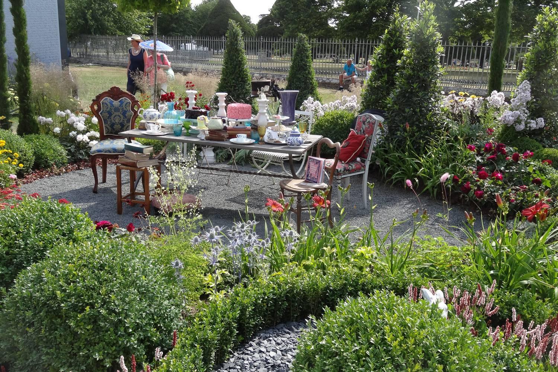 Imagen de una exposición de un juego de té rodeado de flores en el RHS Hampton Court Palace Garden Festival.