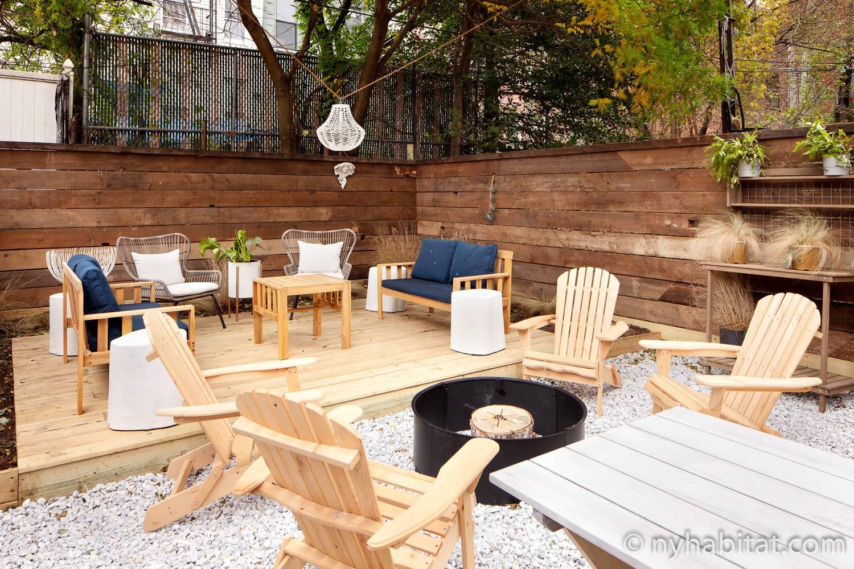 Imagen de una zona ajardinada en NY-17881 con un espacio para hacer hogueras y varios asientos.