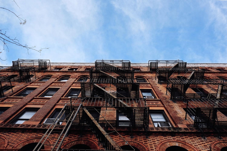 Imagen de una fachada de ladrillo de un edificio de apartamentos con salidas de emergencia en Nueva York.