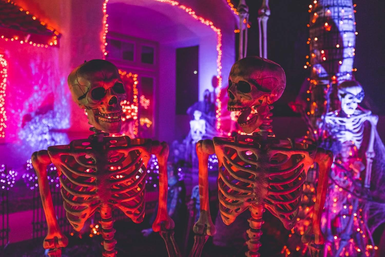 Una imagen de esqueletos brillantes y luces de Halloween en la noche en el Bronx.