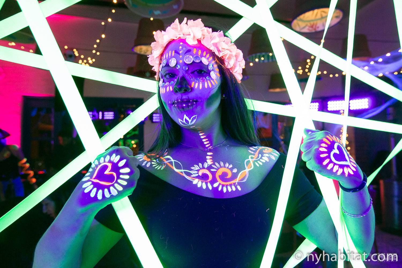 Una imagen de una mujer con resplandor en la oscuridad con pintura de rostro y cuerpo de Halloween rodeada de luces de neón.