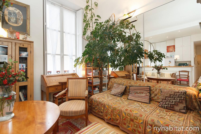 Imagen del salón de este apartamento de París PA-1706 con un sofá, un escritorio y una mesa de comedor.