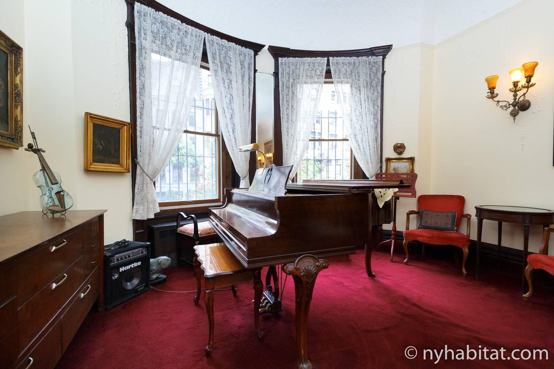 Imagen de un piano en el salón del NY-14656 con una alfombra roja afelpada y muebles tradicionales.