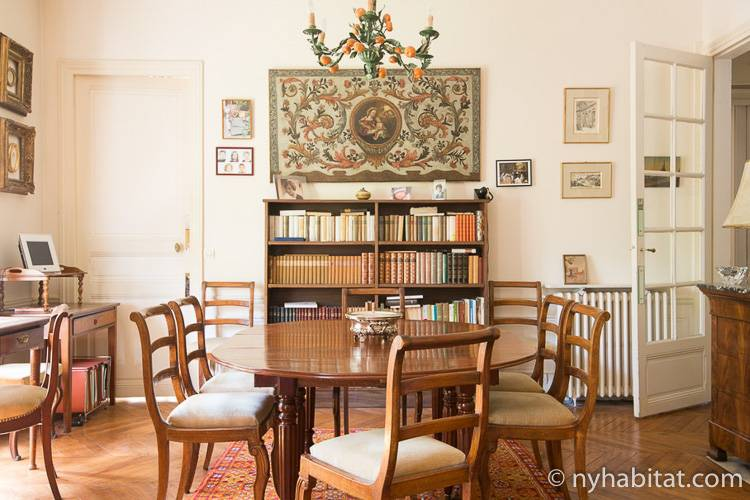 Imagen del apartamento PA-4727 que muestra la mesa de madera del comedor con una obra floral tradicional detrás.