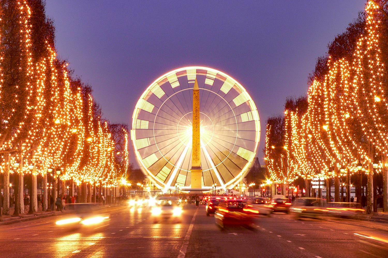 Imagen de la avenida de los Campos Elíseos con árboles envueltos en luces de Navidad iluminando ambos lados de la carretera y una gran noria en el centro.
