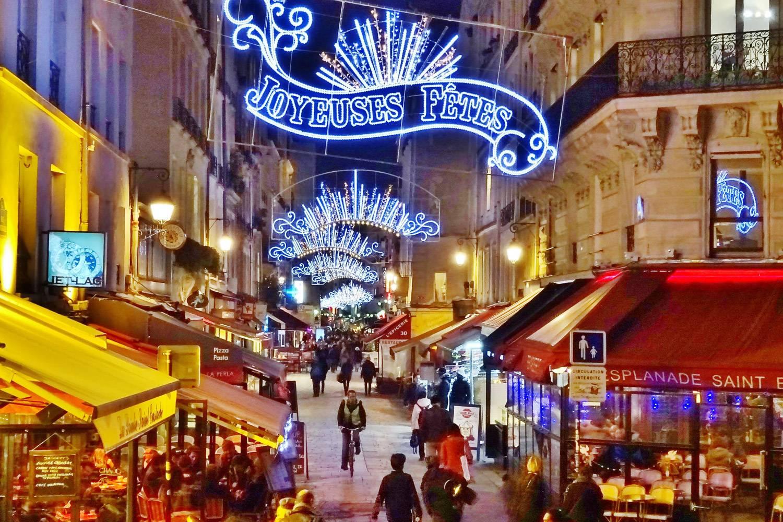 Imagen de la Rue Montorgueil tiendas con puestos en la calle a ambos lados con decoración navideña iluminándose calle arriba.