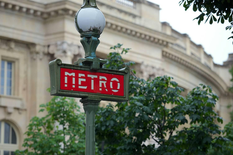 Imagen de una señal de metro roja delante de un edificio en París.