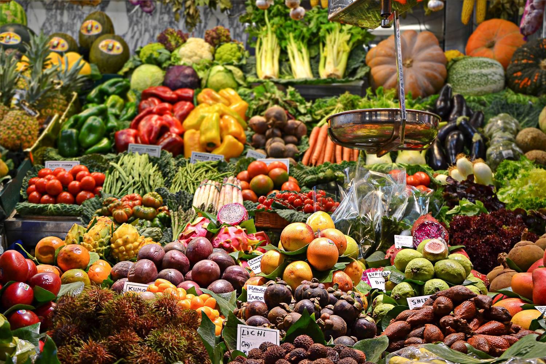 Imagen de frutas y verduras frescas expuestas en un mercado de agricultores, preparadas para la venta.