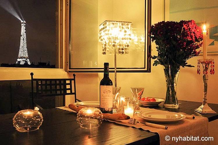 Imagen de una mesa de comedor con velas, una botella de vino y rosas con vistas a la Torre Eiffel desde la ventana