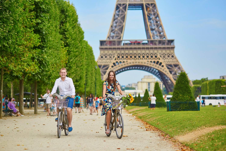 Imagen de una pareja montando en bicicleta en un parque con la Torre Eiffel al fondo