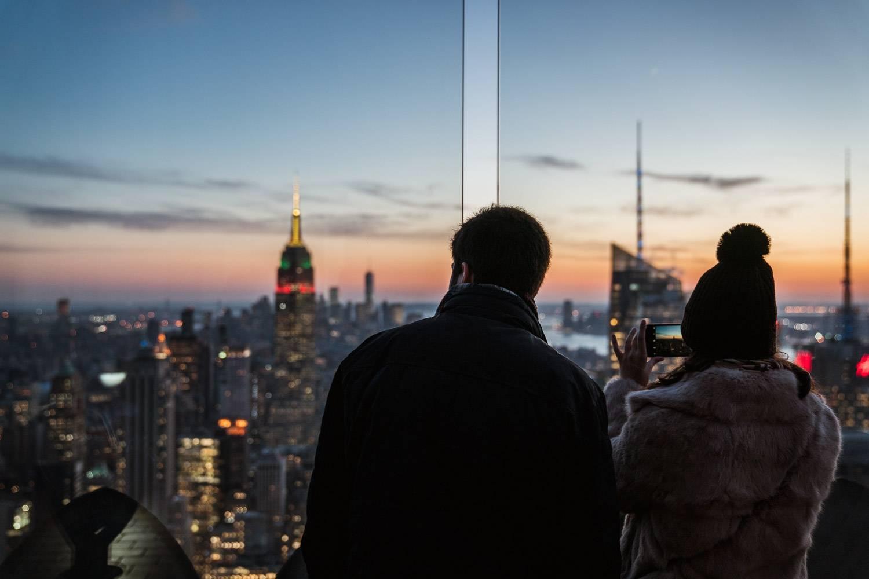 Imagen de una pareja en la cima de un rascacielos al atardecer, con el Empire State Building iluminado en el horizonte.