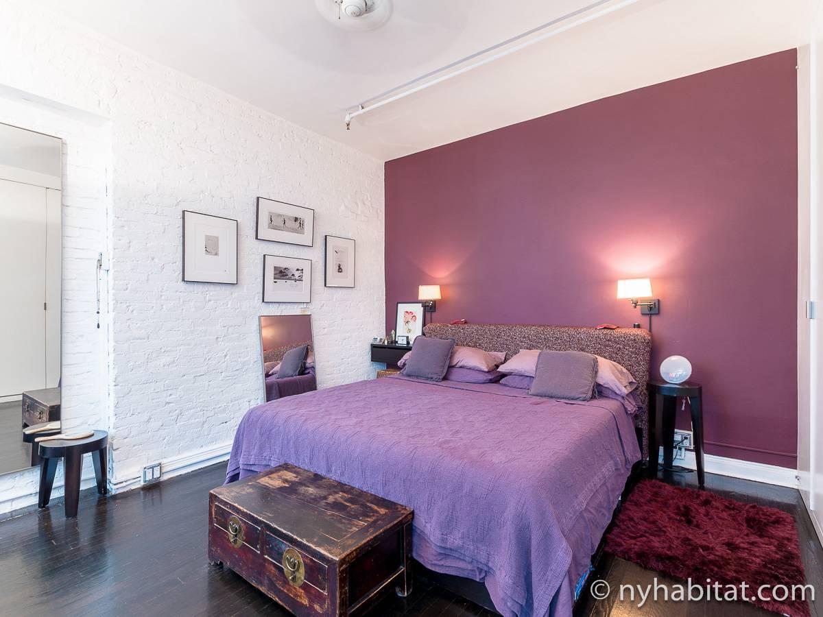 Imagen del dormitorio del apartamento vacacional NY-12330 en el barrio de Gramercy, en Manhattan, con una cama con sábanas violetas, una alfombra roja y paredes con papel rosa