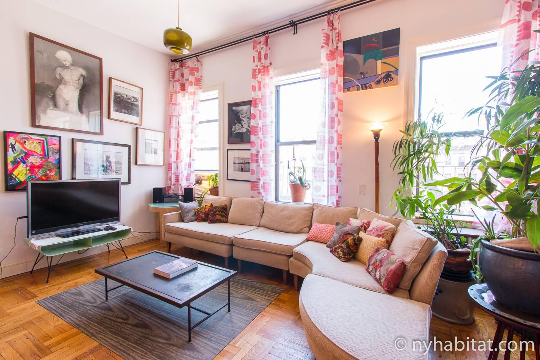Imagen del salón del apartamento amueblado de tres dormitorios NY-16964 en el Lower East Side, con un gran sofá en curva y una televisión